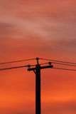 Sunrise And Power Lines. A utility pole silhouetted against the colorful dawn sky Stock Image