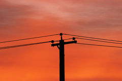 Sunrise And Power Lines. A utility pole silhouetted against the colorful dawn sky Royalty Free Stock Photo
