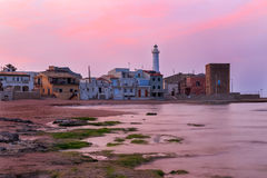 Sunrise at Punta Secca Beach - Montalbano Filming Location. Sunrise at Punta Secca Beach with the lighthouse and the watchtower,Torre Scalambri in Santa Croce royalty free stock photography