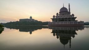 Sunrise At Putrajaya Mosque with reflection. Time lapse 4k Footage of Beautiful Dramatic Sunrise At Putrajaya Mosque with reflection on the water. Pan right stock video footage