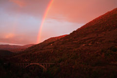 Sunrise with rainbow. Over the hill Stock Photos