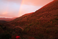 Sunrise with rainbow. Over the hill Stock Images