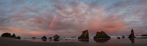 Sunrise and rainbow on ocean beach with cliffs Royalty Free Stock Image