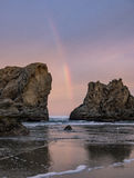 Sunrise and rainbow on ocean beach with cliffs Royalty Free Stock Images
