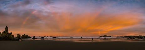 Sunrise and rainbow on ocean beach with cliffs Royalty Free Stock Photos