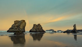 Sunrise and rainbow on ocean beach with cliffs Stock Images