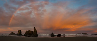 Sunrise and rainbow on ocean beach with cliffs Royalty Free Stock Photography