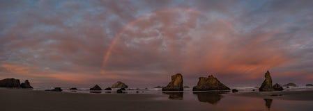 Sunrise and rainbow on ocean beach with cliffs Stock Image