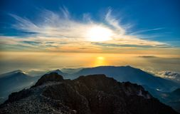 Sunrise rays of light on mountains and dramatic sky Stock Photo