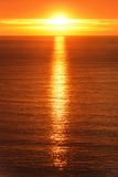 Sunrise reflected on the ocean. Sunrise scenery at the ocean, with the sun reflected on the gold water Stock Image