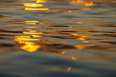 Calm Sea wave sunset view blue water ocean. Sunrise reflected in sea water, reflection in golden color stock image