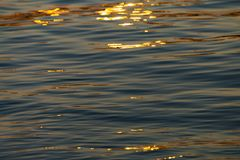 Calm Sea wave sunset view blue water ocean. Sunrise reflected in sea water, reflection in golden color royalty free stock photos