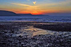 Sunrise reflected in the wet sand and pebbles of Freshwater East beach Stock Image