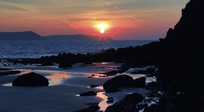 Sunrise reflected in the wet sand and rocks of Freshwater East beach. Pembroke, Wales Stock Image