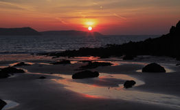 Sunrise reflected in the wet sand and rocks of Freshwater East beach. Pembroke, Wales Stock Images
