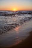 Sunrise reflection on beach sand. Vertical orientation. Pacific ocean coastline Stock Images