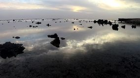 Sunrise and reflection of clouds in the water over the sea, coastal reef at low tide. stock footage
