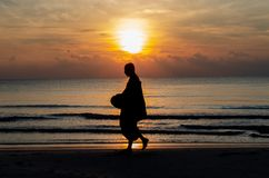 Sunrise with reflection on the sea and beach that have blurred silhouette photo of buddhist monk. Walking alms offering food in the morning on beach of Thailand royalty free stock photos
