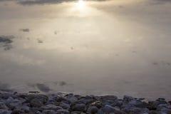 Sunrise reflection at stony beach of Dead Sea Stock Image
