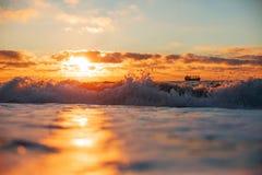 Sunrise reflection on waves stock photography