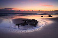 Sunrise reflections on the beach Stock Photography