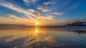 Sunrise reflections at low tide at Tenby in Wales stock images