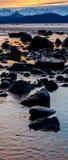 Sunrise Reflections 3. Rocks break up the reflects of dawn on a beach near Homer Alaska Royalty Free Stock Image
