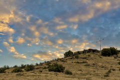 Sunrise on a religious cross on a mountain Stock Photos