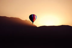 Sunrise ride. This is a hot air balloon over the sandia mountains in albuquerque new mexico at sunrise Stock Photos