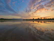 Sunrise on a river. Dramatic sky mirrored in water royalty free stock image
