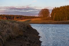 Sunrise by the river bank with the view on a medow and forest.  Stock Image