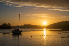 Sunrise on the river lynher with beautiful sky and golden reflections at st germans, cornwall, uk. Sunrise on the river lynher with beautiful sky and golden stock photo
