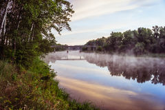 Sunrise on a river with a mist over the water Royalty Free Stock Image