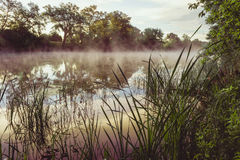 Sunrise on a river with a mist over the water Royalty Free Stock Photography