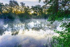 Sunrise on a river with a mist over the water Stock Photography