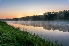 Sunrise on the river, the red sky before sunrise. fog on the river royalty free stock photo