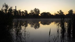 Sunrise on the riverbank. Landscape with silhouettes of reeds and river surface with smoke on the water