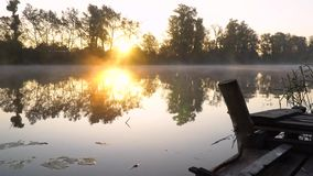 Sunrise on the riverbank. Landscape with wooden fisher bridge, reeds, rising sun and smoke on the water