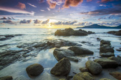 Sunrise at rocky beach in terengganu, malaysia. image taken with long exposure,custom white balance Royalty Free Stock Photo