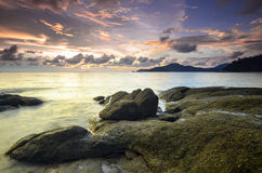 Sunrise at rocky beach in terengganu, malaysia. image taken with long exposure,custom white balance Royalty Free Stock Image