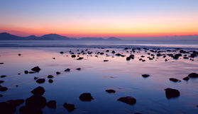 Sunrise on the rocky coast Stock Images