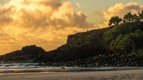 Sunrise rocky coastline. Boy on rocky coastline at sunrise Fingal Head Australia Royalty Free Stock Images