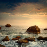 Sunrise on rocky sea coast Stock Images