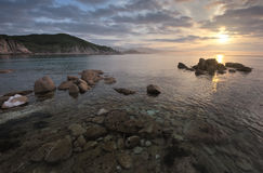 Sunrise on the rocky seashore. Royalty Free Stock Images