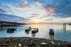 Sunrise rocky shore with fishing boat Royalty Free Stock Images
