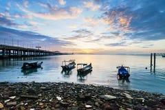 Sunrise rocky shore with fishing boat Stock Photo