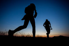 Sunrise running. Silhouettes of two runners during the sunrise Royalty Free Stock Photo