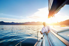 Sunrise sailing boat. Sunrise sailing man on boat in ocean with flare and sunlight on calm morning on the water Royalty Free Stock Photo