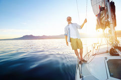 Sunrise sailing boat. Sunrise sailing man on boat in ocean with flare and sunlight on calm morning on the water Stock Image