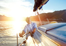 Sunrise sailing boat. Sunrise sailing man on boat in ocean with flare and sunlight on calm morning on the water Stock Photos